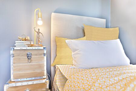 Bedroom with yellow blankets and pillows beside wooden suitcases near the light blue wall, there are wood boxes with silver locks on the floor, the lamp has a flashing bulb over the doll and books Stok Fotoğraf