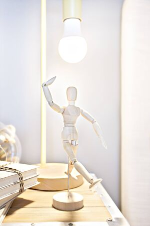 Wooden mannequin isolated under a flashing white lamp near to the and on the wooden box with books and blurred glass jug, this toy is giving a pose like dancing appearance