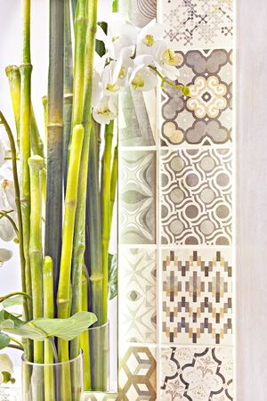 Green bamboo sticks as a decorative item in a glass beside a wall with pattern designs, the white flowers came through the plant with green leaves in a jug