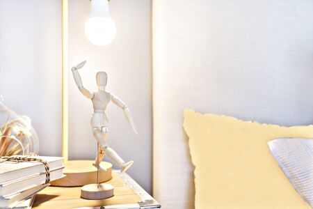 Wooden dummy doll posing and dancing in the blurred bedroom background with a flashing lamp and books on the wooden box near to pillows with yellow designs