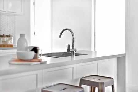 Modern silver taps with a sink on a counter top with plastic benches and the sunlight came through the doors, very clean area.