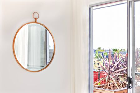 Circle shape mirror with a wooden frame on the wall near the curtain and the window which showed the outside