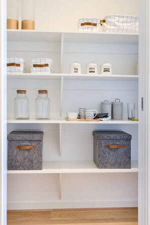 White wooden shelf included metal boxes and mugs with glass bottles next to leather bags in a modern house or market place