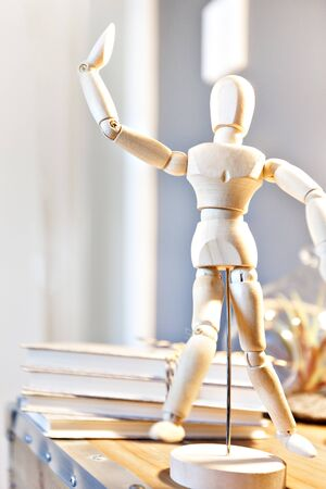 Wooden ball-jointed doll close up posing a dance showing his bones and arms on the blurred wall background with books and round supporter on the wooden top