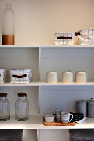 Natural kitchenware in a white wooden shelf, including see through glass bottles and clay mugs with a couple of towels next to garment baskets