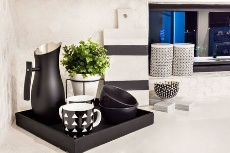 Modern cup and dishes beside flower vase and jug on a black wooden tray on countertop of the kitchen