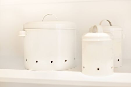 Modern utensil pots in white color ceramic  with ingredients on a wooden shelf, colorful food cans in kitchen, very clean area, perfect lightning.