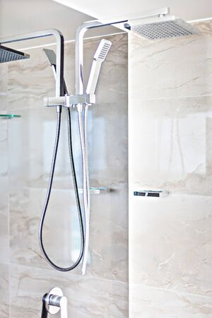 A contemporary shower area with tiled walls