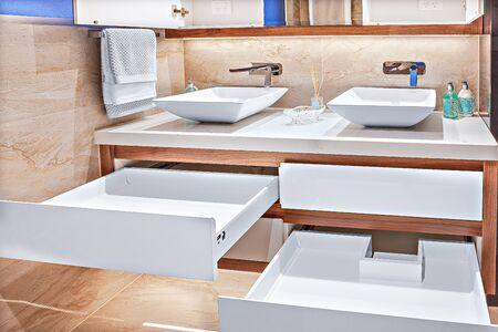 Lavabos de tocador cuidadosamente diseñados con gabinetes espaciosos y grifos de diseñador Foto de archivo