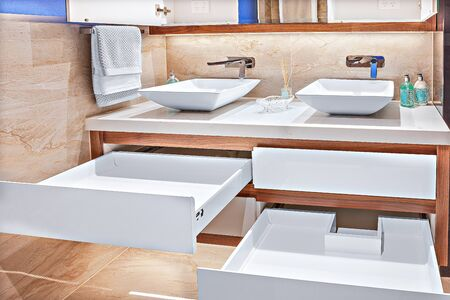 Neatly-designed vanity basins with spacious cabinets and designer taps Stock fotó