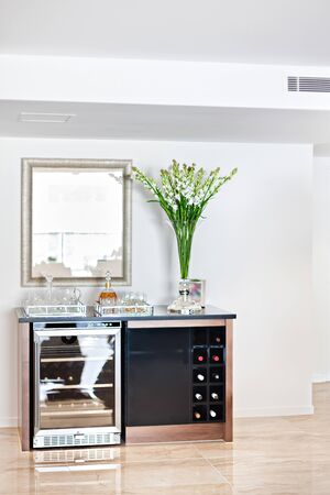 A minimalist home bar with a beer chiller, a wine rack, and barware Imagens