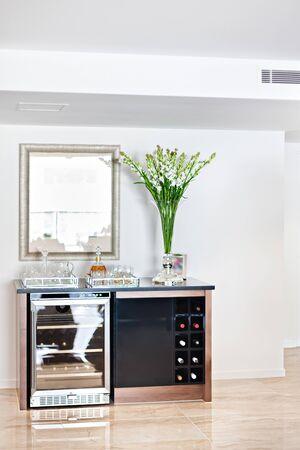 Un bar casalingo minimalista con un refrigeratore di birra, un portabottiglie e articoli da bar Archivio Fotografico