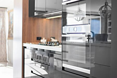 Neatly-designed kitchen cabinets with gas hob on the counter and electronic equipment