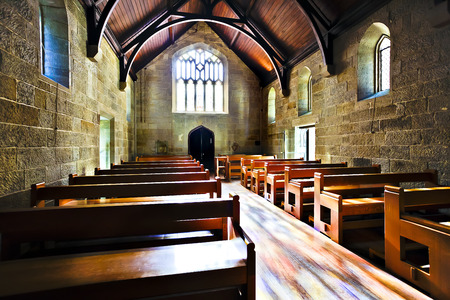 Old style of the Church room with wooden chairs and stone walls illuminated by sunlight came from the window