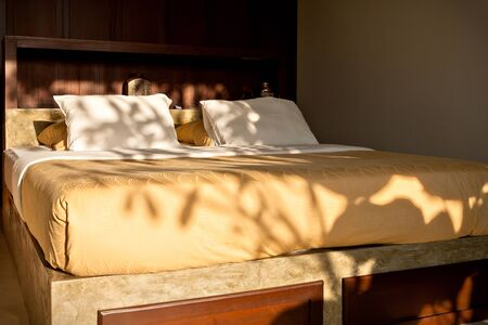 Closeup of a traditional wooden bed and  pillows illuminated with sunlight in a house
