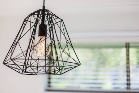 Close view of a contemporary cage design ceiling light with the bulb switched on