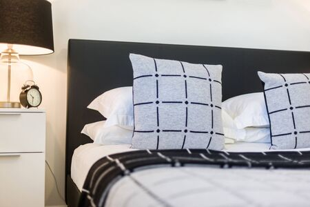 View of two box design cushions and 4 plain white pillows kept on luxurious bedding