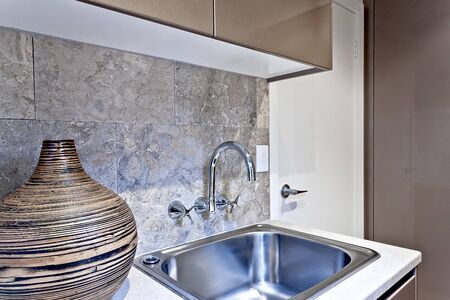 Wooden or ornamental vase or pot beside silver faucet and washstand fixed to wall tile