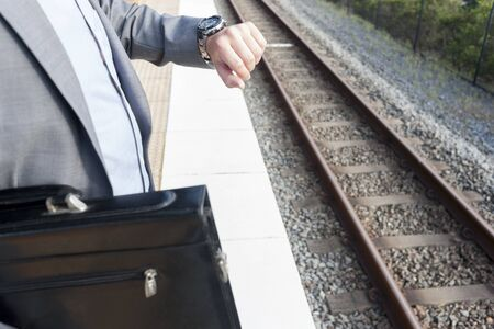 Office bag and watch on businessmans hand, sunlight around the area, morning time and rush hours, floor is tiled, sky is clear. Stok Fotoğraf
