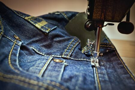 Machine sewing a blue jean close up with buttons and yarn, thread under blue light Zdjęcie Seryjne