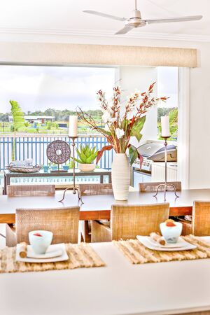 Kitchen tools with ceramic items on dining table, river also forest can see behind fence, colorful photograph from lightning, daytime scene, perfect lights arround.