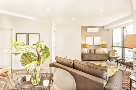 Flower vase near living room and tables, flowers pot and ceramic cups on the glass table, leaves are more colorful and attractive, tiled floor close to walls, city view can see through windows.
