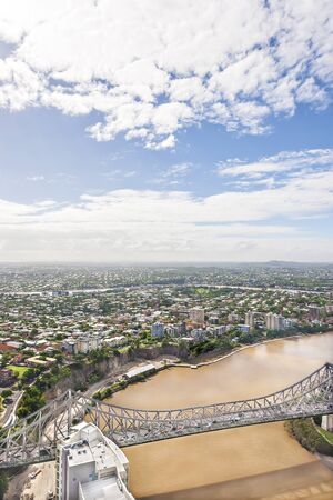 Long bridge on muddy water near city and sky, river is brown color with mud water, bridge has lots of vehicles, city has huge buildings and houses, green trees and grass have on ground. Stockfoto