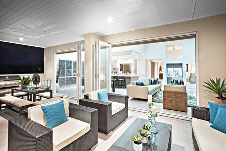 Salon et meubles modernes et colorés, espace luxueux avec vêtements de cuisine et vue naturelle, bougies à côté de vases à fleurs sur la table, évier fixé au mur près d'une cuisinière à gaz, aquarium près des murs.