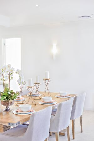 Dining area with a wooden table and chairs in a room with white walls, there is a door which spreading sunlight