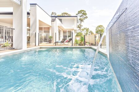 Modern beautiful swimming pool near luxury home entrance, shiny sunlight arround the area, beautiful green trees on garden, sky has white clouds.