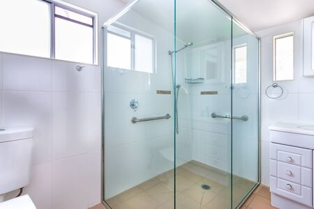Spacious shower cabin with glass walls and safety handles Фото со стока - 131853083