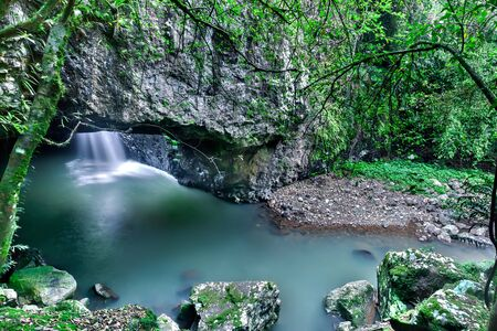 Small river and waterfall in the cave under the huge rock with mossy stones and trees
