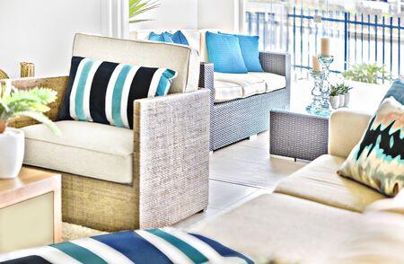 Comfortabele nieuwe bankstel in de kamer, kussens hebben een aantal ontwerpen, glazen kaarsen op tafel, vloer is betegeld, perfecte verlichting, zonlicht rondom het gebied, prachtige plek.