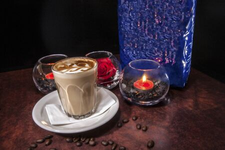 Coffee glass on paper with plate, milk cup and background, colorized photograph including perfect lights, very tasty hot drink of luxury house. Zdjęcie Seryjne
