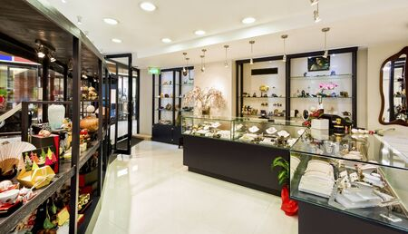 Jewelry and antiques in a fancy shop show on showcases with the lights hanging, there are very colorful and traditional items on the racks to buy