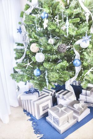 Green tree with gift boxes, christmas decoration with shiny stars, colorful leaves and metal balls, perfect lightning, specially use for festivals, daytime photograph with designs. 스톡 콘텐츠