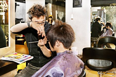 Modern Asian haircut in a luxury saloon with stylist cuts, the barber is cutting the boys hair carefully Stock fotó