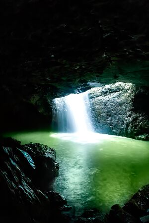 Shiny waterfall flows in the dark stone cave that brighten with the sunlight, the water turns green because of the light