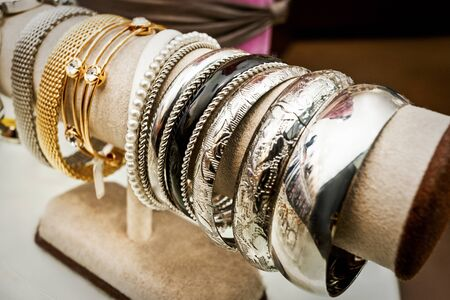 Shiny bracelets with modern carve in silver and gold color on the wooden dummy, there are different sizes and styles available in the store Standard-Bild