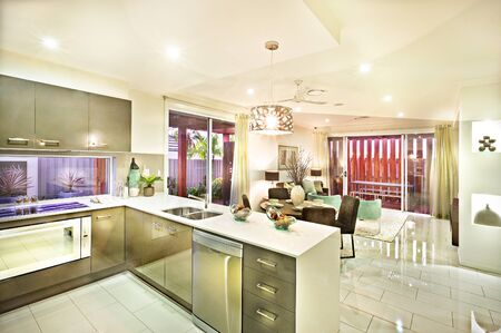 Modern kitchen and the hanging lights flashing over the dining area with a reflective tile floor and door entrance Foto de archivo - 131853445