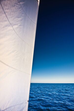 A yacht sail with a clear sea and sky