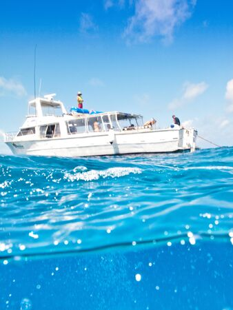 A yacht on the sea with people onboard on a sunny day Banco de Imagens