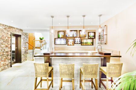Latest dining room with furniture and walls, chairs area made in woods, floor is tiled, sink can see on the table, vine bottles in wall cupboards, perfect lights balancing, home interior photograph. Stok Fotoğraf
