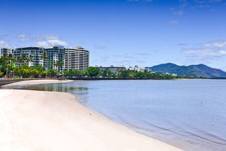 An empty beach with buildings and mountains in the background