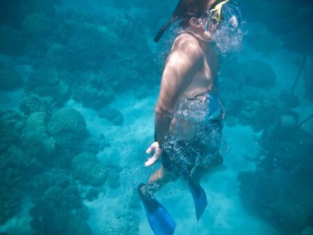 A man wearing diving goggles and flippers swimming upwards