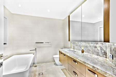 Colorful wash room with bath tub and mirrors, sink has attached to table, mirror is shiny, glass bottle on tiled-table, perfect lights balancing, home interior photograph. Stok Fotoğraf