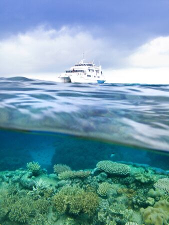 A partially submerged photograph of coral reef and a sailing yacht