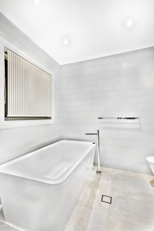 White ceramic bathing tub in luxury room, window is closed, walls are colorful, floor is tiled, perfect lights balancing, home interior photograph, very clean place. Stok Fotoğraf
