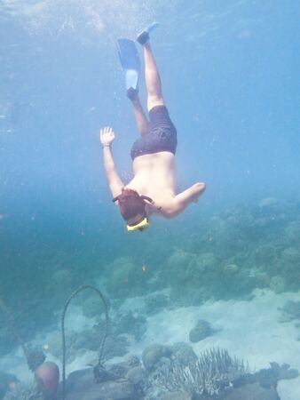A man swimming underwater with diving goggles and flippers