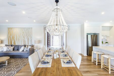 A beautiful chandelier hanging over the dining table, parting the living room area and the kitchen counter. Foto de archivo - 131854141